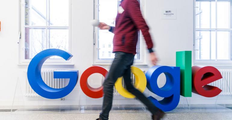 man walking by google logo