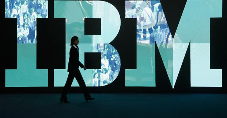 A person walks in front of an IBM logo.