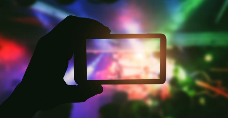 taking photo on smartphone at concert
