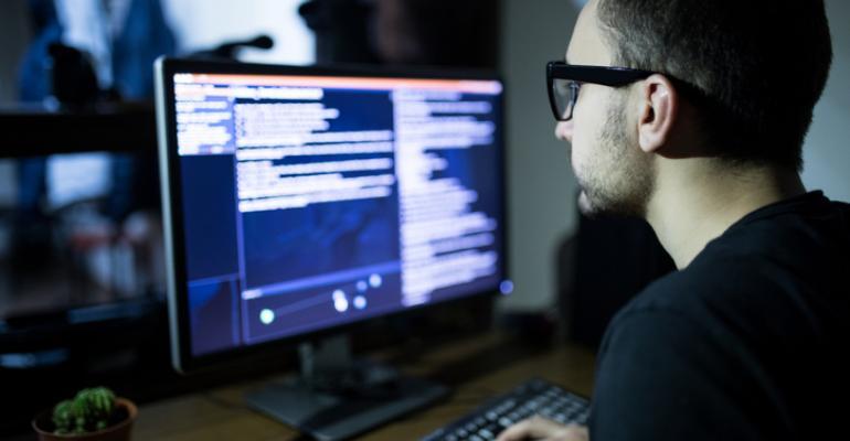 male hacker on computer in dark room