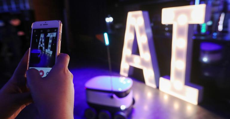 An attendee photographs an autonomous parcel delivery robot, developed by Starship Technologies Ltd. at the AI Congress in London, U.K., on Tuesday, Jan. 30, 2018. After decades of premature promises, artificial intelligence (AI) is finding its way into businesses from hedge funds to law firms tobeer makers, as the line between ordinary software and AI software has blurred and cloud computingmakes AI available to small companies as well as large. Photographer: Luke MacGregor/Bloomberg