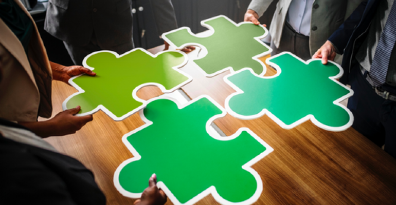 Four people holding four jigsaw puzzle pieces.png