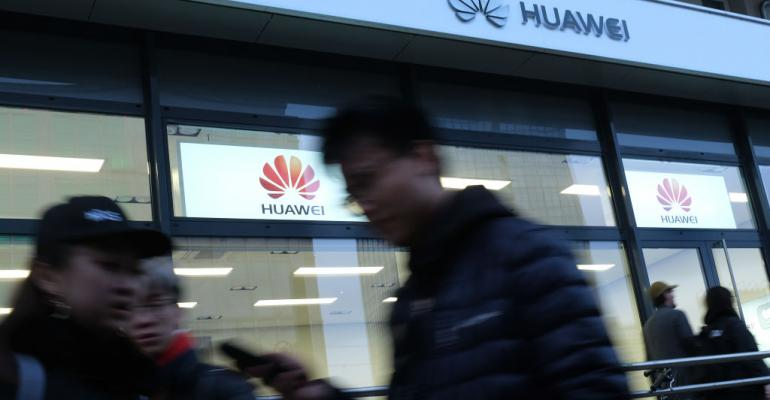 People walk past a Huawei store