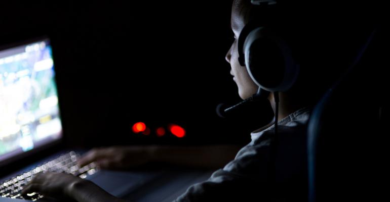 A woman plays a computer game in the dark