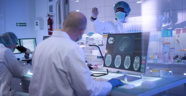 Multi ethnic doctors research team studying brainwave scanning wearing masks.jpg