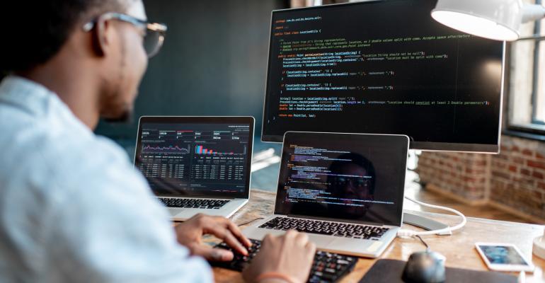 Programmer writing code looking at monitors.jpg
