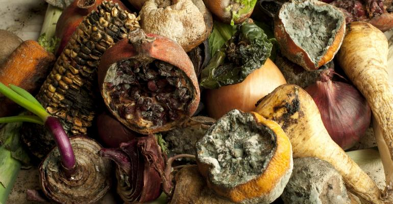 Rotten fruit and vegetables clustered together on a table top