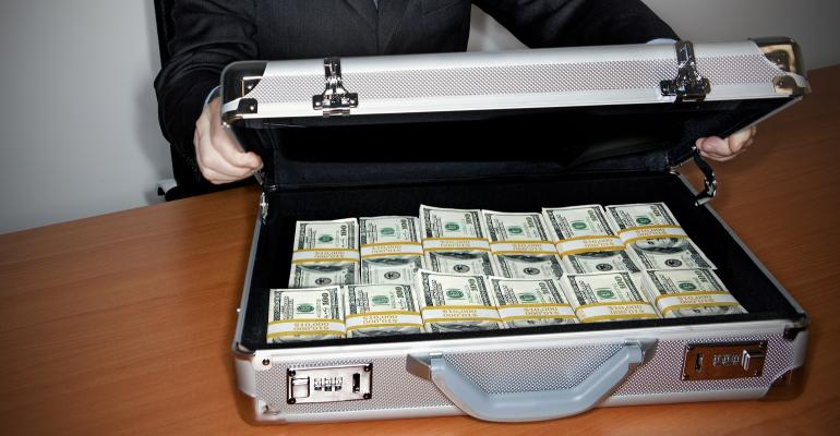 Man holding silver briefcase full of $100 bills