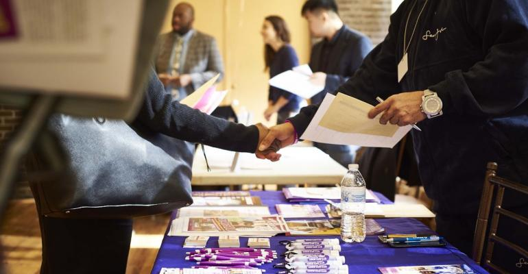 A job seeker, left, shakes hands with a representative during a Shades of Commerce Career Fair in the Brooklyn borough of New York, U.S., on Saturday, Feb. 17, 2018. Photographer: Gabby Jones/Bloomberg