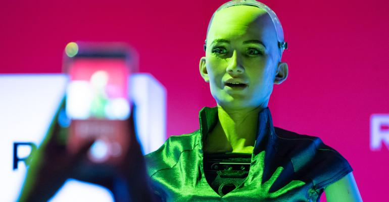 "An attendee takes a photograph of Hanson Robotics Inc. humanoid robot ""Sophia"" during the Rise conference in Hong Kong, China. Photographer: Anthony Kwan/Bloomberg"