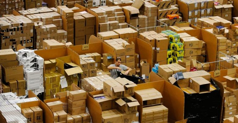 A worker picks an item for a customer's order at an Amazon.com Inc. fulfillment center in Peterborough, U.K. Photographer: Luke MacGregor/Bloomberg