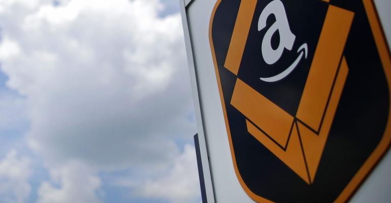 The Amazon.com logo is displayed outside the company\'s fulfillment center in Kenosha, Wisconsin, U.S., on Tuesday, Aug. 1, 2017. Amazon.com Inc. held a giant job fair at nearly a dozen U.S. warehouses as part of its effort to hire 100,000 people in the U.S. by 2018. Photographer: Jim Young/Bloomberg