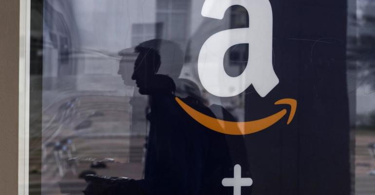 A student is reflected in the window of an Amazon.com Inc. kiosk on the University of California, Berkeley campus in Berkeley, California, U.S., on Wednesday, Oct. 12, 2016. By the end of the year, Amazon will have staffed pickup kiosks serving more than 500,000 college students at 16 schools around the country. Students order items from Amazon.com Inc. and retrieve them from new pickup lockers. Photographer: David Paul Morris/Bloomberg