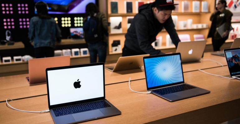 Apple Inc. MacBook Pro laptop computers sit on display at the company's Williamsburg store in the Brooklyn borough of New York, U.S., on Friday, May 20, 2017. Apple Chief Executive Officer Tim Cook said in May that the company planned to invest at least $1 billion to back advanced manufacturing companies in the U.S. and help create jobs in the industry. Photographer: Mark Kauzlarich/Bloomberg