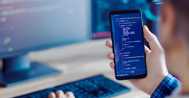 man developing code on laptop and phone