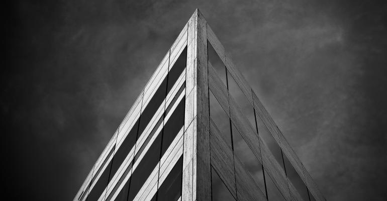 A sharp corner of a corporate structure against a stormy backdrop