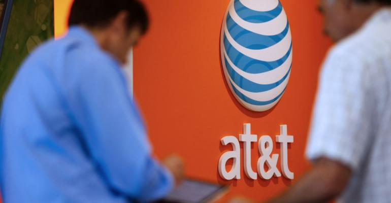 An employee helps a customer at an AT&T Inc. store in Manhattan Beach, California, U.S. Photographer: Patrick T. Fallon/