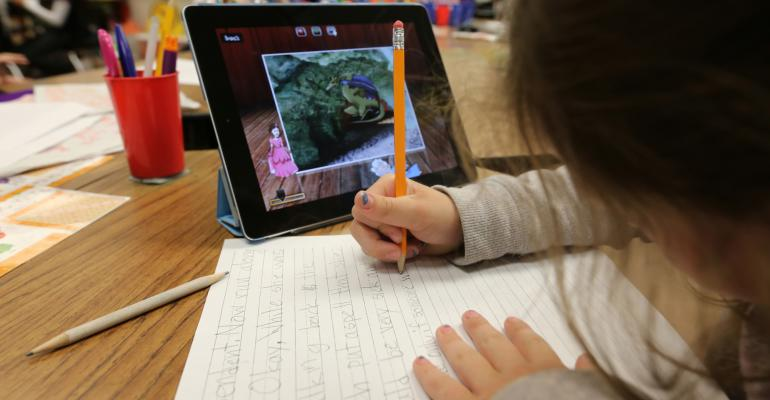 A second grader uses an Apple Inc. iPad while studying in her classroom at Park Lane Elementary school, in the Canyons School District, in Sandy, Utah, U.S. on Monday, May 20, 2013. As technology becomes more integrated in the classroom, in addition to Apple, other manufacturers including Microsoft corp., Amazon.com Inc., Samsung Electronics Co., and News Corp.s Amplify are turning toward education. Photographer: George Frey/Bloomberg via Getty Images