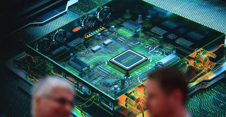 Visitors stand near a large graphic of a computer chip motherboard at the Kaspersky Lab pavilion at the CeBIT 2017 tech fair in Hannover, Germany, on Tuesday, March 21, 2017. Leading edge technologies in the digital world are showcased in this annual event which runs March 20 - 24.