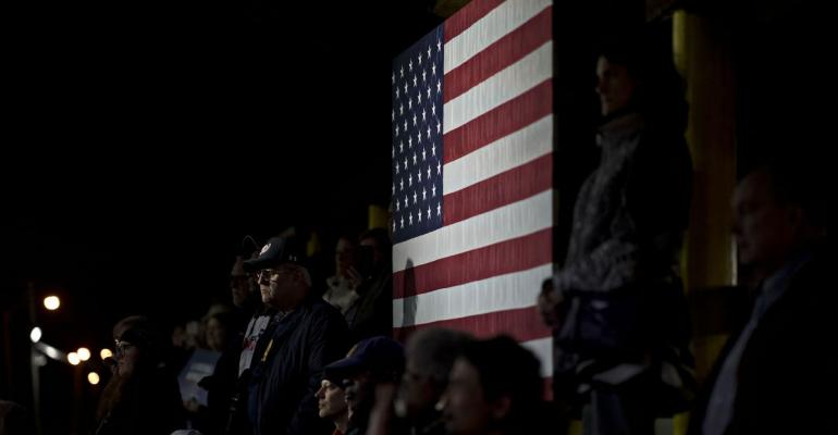 Attendees stand next to the American flag while listening to Senator Tim Kaine, a Democrat from Virginia, not pictured, speak during a campaign rally in Manassas, Virginia, U.S., on Sunday, Nov. 4, 2018. State Senator Jennifer Wexton leads incumbent House Republican Barbara Comstock 54% to 43% ahead of Tuesday's midterm election, according to a Washington Post-Schar School poll. Photographer: Andrew Harrer/Bloomberg