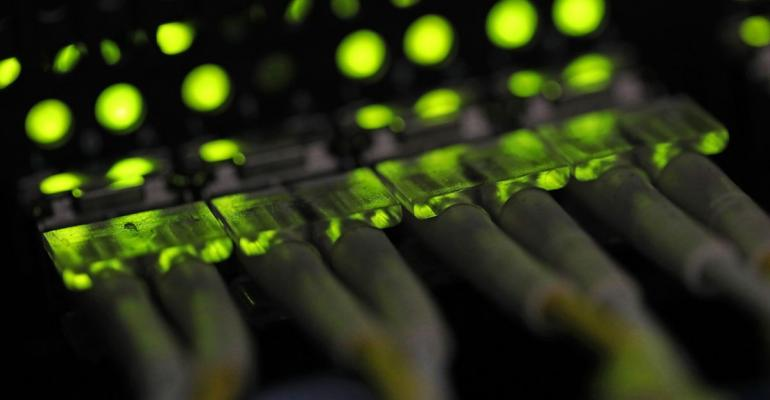 Green light illuminates data cable terminals inside a communications room. Photographer: Chris Ratcliffe/Bloomberg