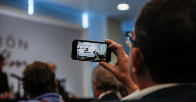 An attendee uses a mobile phone to record a Facebook Inc. Live stream of Carlos Slim, chairman emeritus of America Movil SAB, speaking during a press conference in Mexico City, Mexico, on Monday, April 16, 2018. Slim said that Mexico has plenty of advantages in the NAFTA negotiations. Photographer: Alejandro Cegarra/Bloomberg