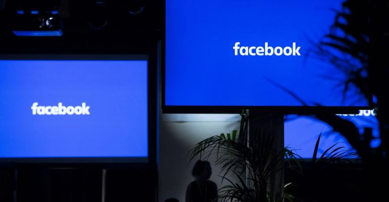 """The Facebook Inc. logo sits on screens ahead of the global launch event of """"Workplace"""" at the Facebook Inc. offices in London, U.K. Photographer: Jason Alden/Bloomberg"""