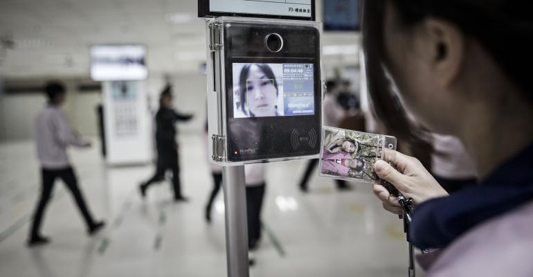 A woman tests facial recognition on her handheld device