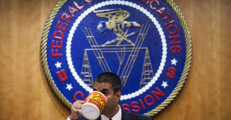 Ajit Pai, chairman of the Federal Communications Commission (FCC), drinks from an oversized coffee mug during an open meeting in Washington, D.C., U.S. Photographer: Zach Gibson/Bloomberg