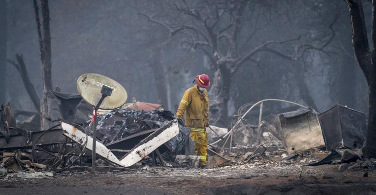 A firefighter searches a burned-out building in Paradise, California, U.S., on Thursday, Nov. 15, 2018.  Photographer: David Paul Morris/Bloomberg