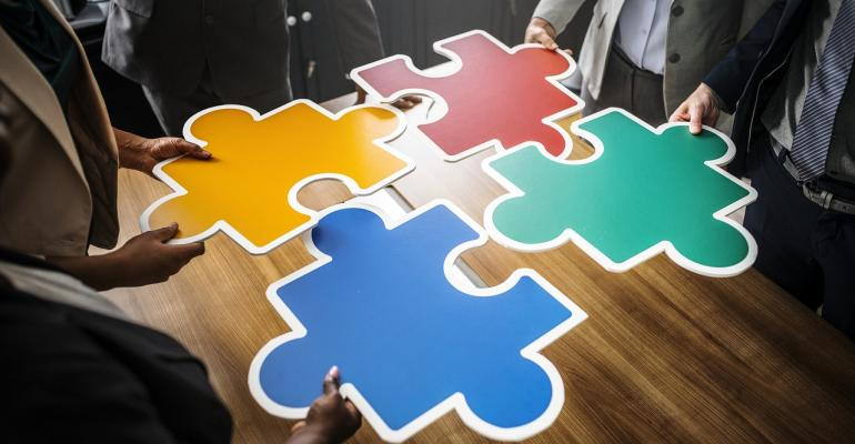 Four Colored Jigsaw Pieces Being Put Together