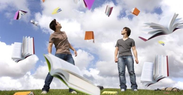 Two young men on grass with SQL Server books flying in the air