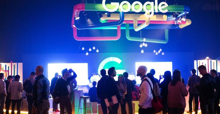 Indoor gathering with a few dozen people standing underneath a large hanging Google logo