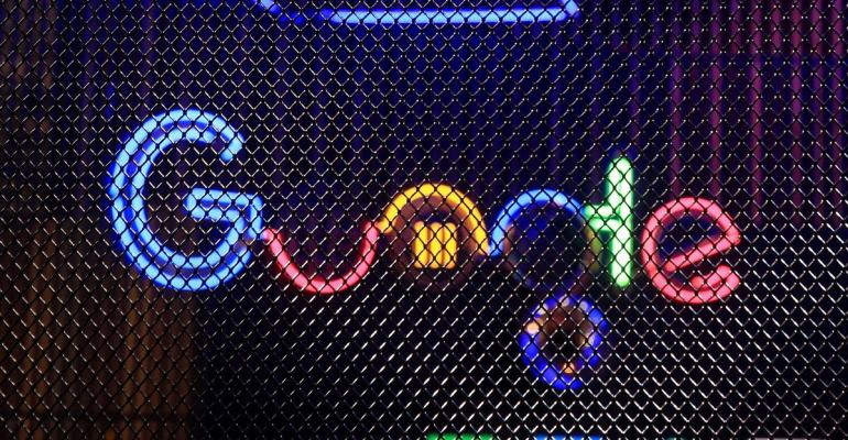 The Google Inc. logo hangs illuminated at the company's exhibition stand at the Dmexco digital marketing conference in Cologne, Germany. Photographer: Krisztian Bocsi/Bloomberg