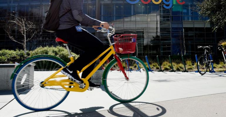 An emplyee passes the Google Inc. offices in Mountain View, California. Photographer: Michael Short/Bloomberg
