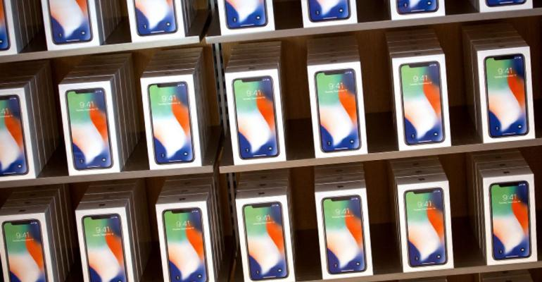 Apple Inc. iPhone X smartphones are displayed during the sales launch at a store in New York, U.S., on Friday, Nov. 3, 2017. The $1,000 price tag on Apple Inc.'s new iPhone X didn't deter throngs of enthusiasts around the world who waited -- sometimes overnight -- in long lines with no guarantee they would walk out of the store with one of the coveted devices. Photographer: Michael Nagle/Bloomberg
