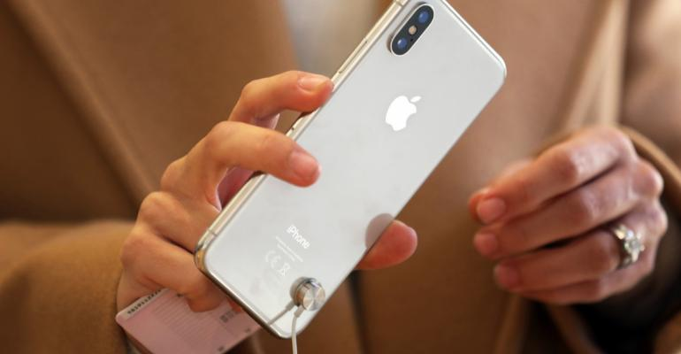 A customer tests an iPhone X smartphone at the Apple Inc. store on Regent Street in London, U.K., on Friday, Nov. 3, 2017. Supported by resurgent iPad and Mac sales, the 10-year anniversary iPhone will help push revenue to a record high of $84 billion to $87 billion in the quarter ending in late December, Apple said in a statement. Photographer: Luke MacGregor/Bloomberg