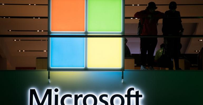 Customers stand near the Microsoft Corp. logo during the Microsoft Corp. Xbox One X game console global launch event in New York, U.S., on Monday, Nov. 6, 2017. As Microsoft Corp. begins selling a new Xbox console, the focus of its video-game unit is shifting toward software and services. The company plans to increase investment in developing in-house video games. Photographer: Mark Kauzlarich/Bloomberg