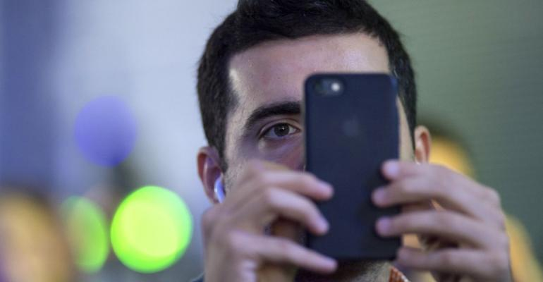 An attendee uses an Apple Inc. iPhone to take a photograph during the TechCrunch Disrupt 2017 in San Francisco, California, U.S., on Monday, Sept. 18, 2017. TechCrunch Disrupt, the world's leading authority in debuting revolutionary startups, gathers the brightest entrepreneurs, investors, hackers, and tech fans for on-stage interviews. Photographer: David Paul Morris/Bloomberg