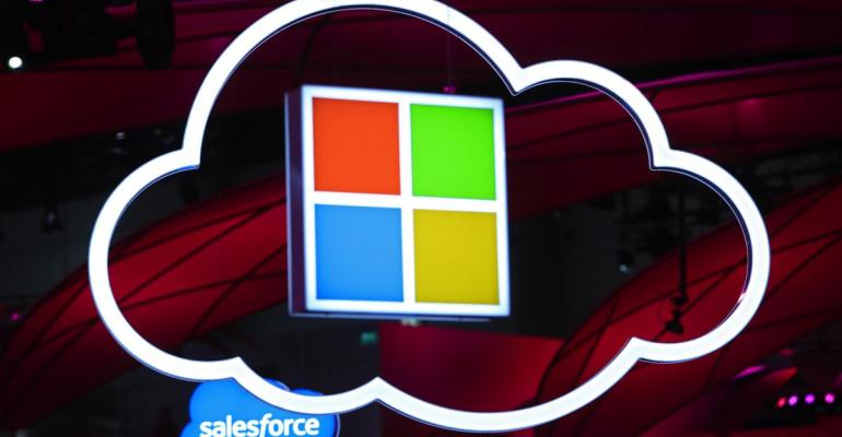 Microsoft Corp. logo, center, hang beside an illuminated iCloud icon at the CeBIT 2017 tech fair in Hannover, Germany. Photographer: Krisztian Bocsi/Bloomberg
