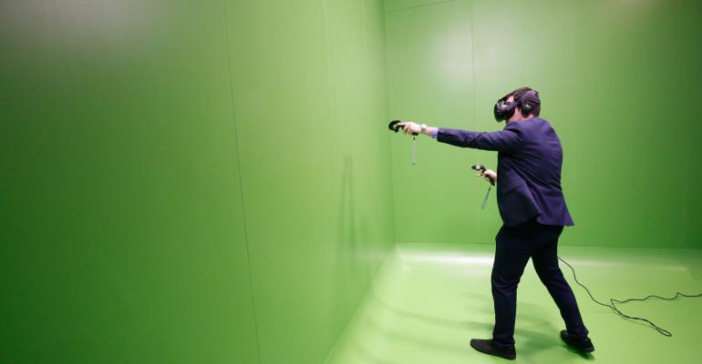 An attendee uses a Vive virtual reality (VR) headset, manufactured by HTC Corp., on the opening day of the Mobile World Congress (MWC) in Barcelona, Spain, on Monday, Feb. 27, 2017. Photographer: Pau Barrena/Bloomberg