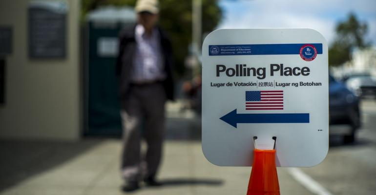 """A pedestrian walks towards a """"Polling Place"""" sign during the presidential primary election in San Francisco, California, U.S., on Tuesday, June 7, 2016. Hillary Clinton secured the delegates required to claim the Democratic presidential nomination Monday, putting further pressure on Bernie Sanders to exit the race. Photographer: Bloomberg/Bloomberg"""