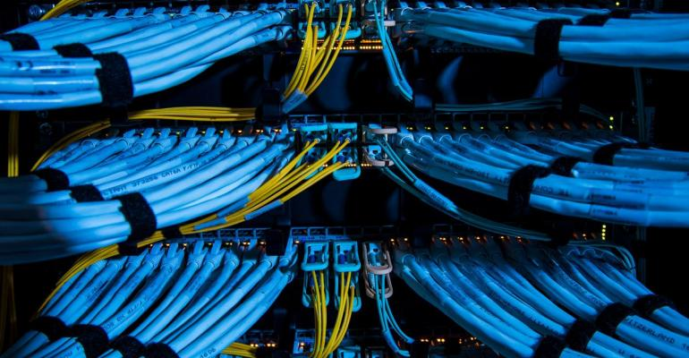 Fiber optic cables, center, and copper Ethernet cables feed into switches inside a communications room at an office in London, U.K. Photographer: Jason Alden/Bloomberg