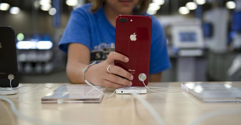 A customer views an Apple Inc. iPhone on display for sale at a store in San Antonio, Texas. Photographer: Callaghan O'Hare/Bloomberg