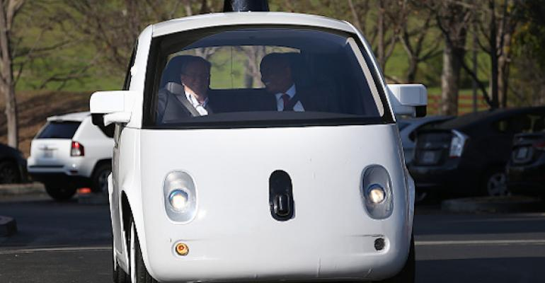 Driver and passenger in a small white self-driving car