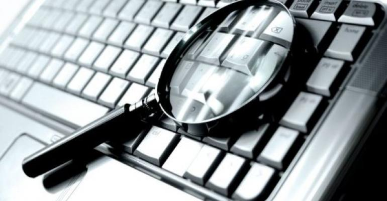 magnifying glass laying on a computer keyboard