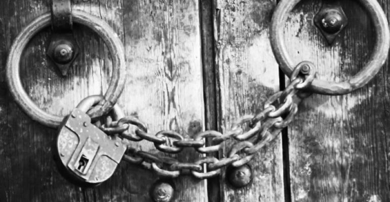 black and white image of wooden door with chain and padlock on its handles