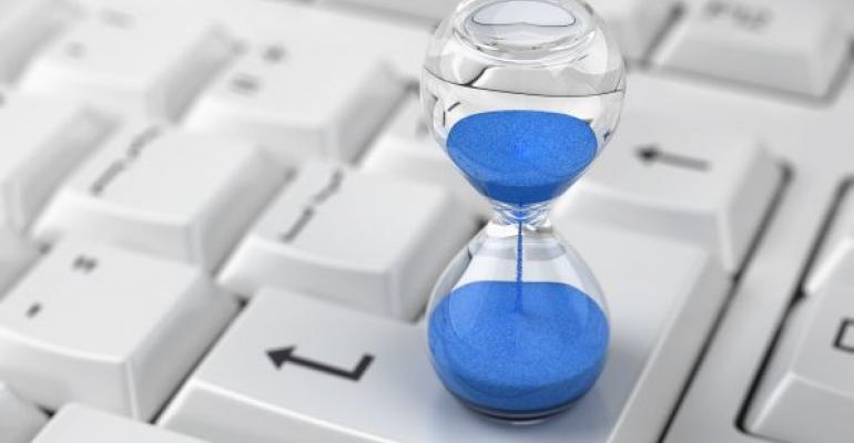 hourglass with blue sand on a computer keyboard