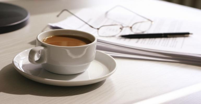 coffee in cup with papers glasses and pen in background