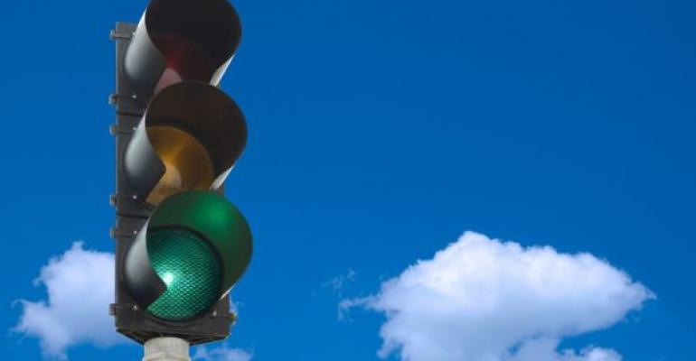 traffic light on green against blue sky and clouds